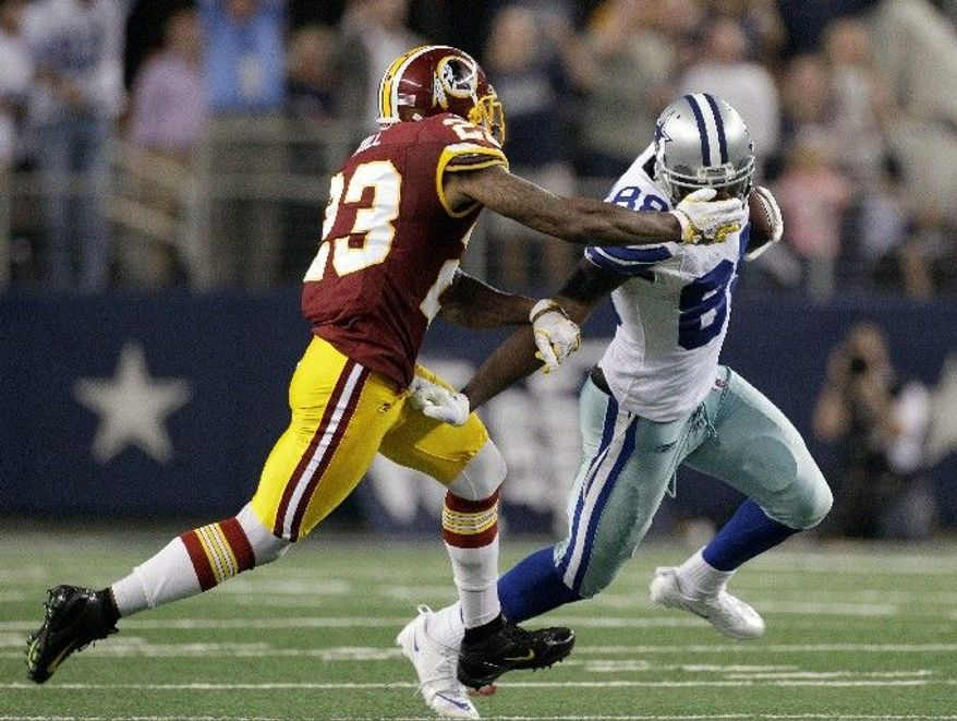 Washington Redskins cornerback DeAngelo Hall grabs Dallas Cowboys wide receiver Dez Bryant's face mask during the second half of an NFL football game on Monday, Sept. 26, 2011, in Arlington, Texas. The Cowboys won 18-16. (AP Photo/Tony Gutierrez)