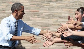 "President Obama shakes hands at Abraham Lincoln High School in Denver on Tuesday. ""He's a good president, but there's no jobs,"" a student said. (Associated Press)"