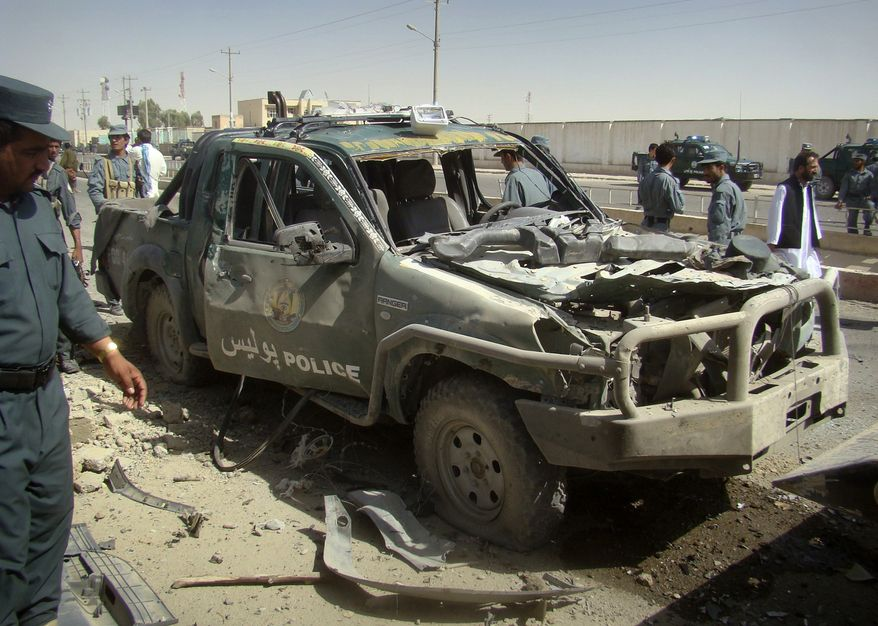 An Afghan police officer (left) looks at a police vehicle damaged in a suicide attack in Lashkar Gah in Afghanistan's Helmand province on Tuesday, Sept. 27, 2011. (AP Photo/Abdul Khaleq)