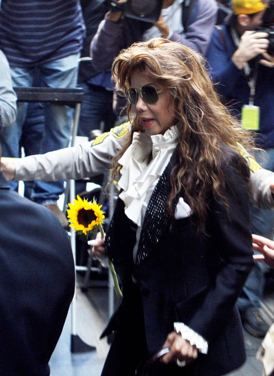 Holding a sunflower given her by a fan, Michael Jackson's sister Latoya arrives as the involuntary manslaughter trial for Dr. Conrad Murray.   (AP Photo/Reed Saxon)