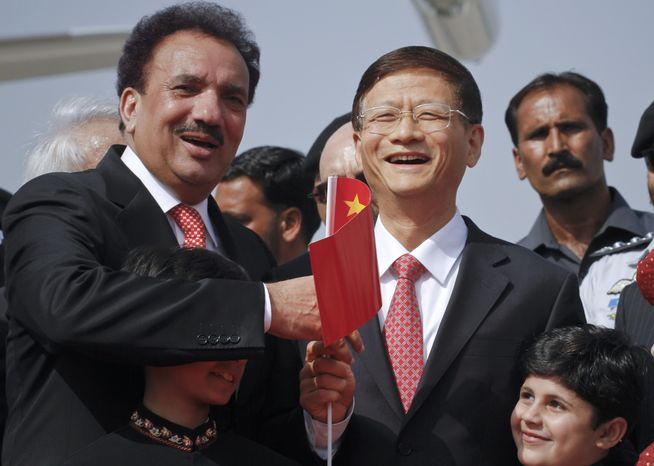 Chinese Public Security Minister Meng Jianzhu (second right) and Pakistani Interior Minister Rehman Malik (left) wave Chinese flag upon Jianzhu's arrival at Chaklala airbase in Rawalpindi, Pakistan on Sept. 26, 2011. (Associated Press)