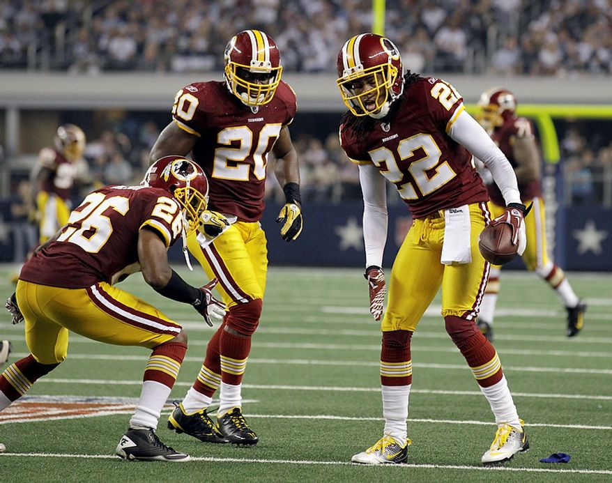 Washington Redskins defensive back Kevin Barnes (right) celebrates after an interception of a Dallas Cowboys pass with teammates Josh Wilson (26) and Oshiomogho Atogwe (20) during the second half of an NFL football game on Monday, Sept. 26, 2011, in Arlington, Texas. (AP Photo/Tony Gutierrez)