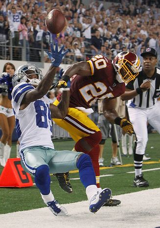 Washington Redskins free safety Oshiomogho Atogwe knocks the pass away from Dallas Cowboys wide receiver Kevin Ogletree during the second half of an NFL football game Monday, Sept. 26, 2011, in Arlington, Texas. (AP Photo/LM Otero)