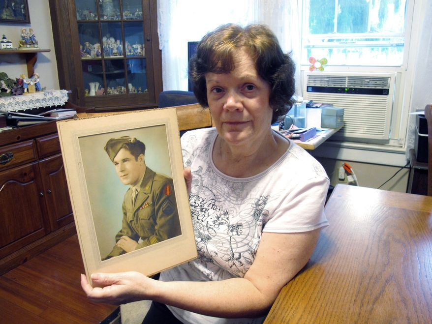 George Wright's daughter, Ann Patterson, holds a photo of her father. (Associated Press)