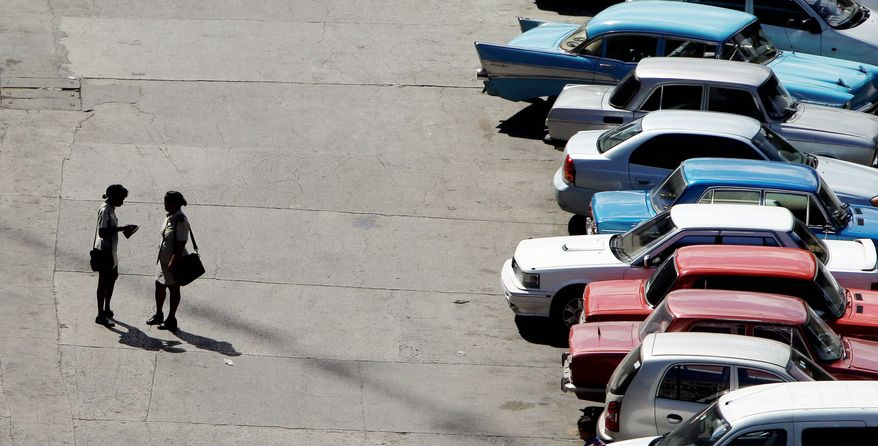 Two customs officers speak in a Havana, Cuba, car lot. Cuba legalized the sale and purchase of automobiles for all citizens Wednesday. Under the law, buyers and sellers must each pay a 4 percent tax, and buyers must make a sworn declaration that the money used for the purchase was obtained legally. (Associated Press)