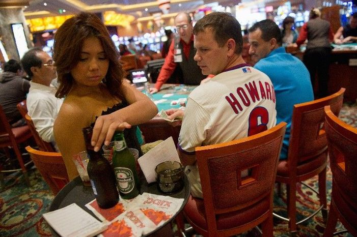 Darine Son, a cocktail waitress, serves beer to Bob Schank while he plays cards at a blackjack table last week in Parx Casino, near Philadelphia. The gambling house and nine others in Pennsylvania are providing thousands of jobs and raking in billions of dollars in tax revenue for the state. But there is opposition to the gambling on moral grounds. (Andrew Harnik/The Washington Times)
