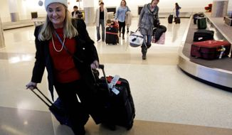 **FILE** Holiday travelers collect their luggage Dec. 21, 2010, at the San Jose International Airport in San Jose, Calif. (Associated Press)