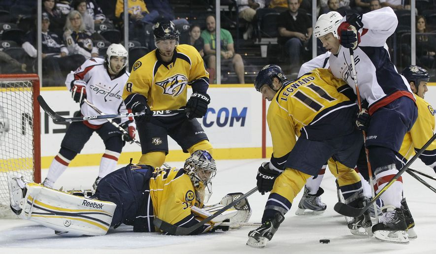 Nashville Predators goalie Pekka Rinne (35) watches as Predators center David Legwand (11) and Washington Capitals right wing Mike Knuble (front right) fight for the puck in the third period of a preseason NHL hockey game on Wednesday, Sept. 28, 2011, in Nashville, Tenn. Capitals center Mathieu Perreault (back left) and Predators defenseman Kevin Klein (back right) look on. (AP Photo/Mark Humphrey)