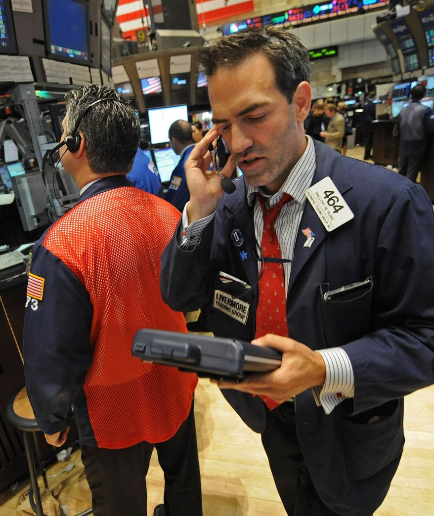 ** FILE ** Gregory M. Rowe with Livermore Trading Group Inc. works on the floor of the New York Stock Exchange on Thursday, Sept. 22, 2011. (AP Photo/Louis Lanzano, File)