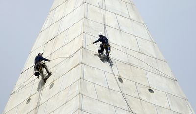 Emma Cardini, a civil engineer from Melrose, Mass., right, and a member of the difficult access team, dangles by a rope more than 500 feet above ground, with co-worker Daniel Gach, as they inspect the exterior of the Washington Monument on the National Mall in Washington, Thursday Sept. 29, 2011. (AP Photo/Manuel Balce Ceneta)