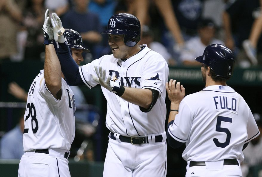 Tampa Bay Rays' Evan Longoria, center, celebrates with teammates John Jaso, left, and Sam Fuld after his three-run home run off New York Yankees relief pitcher Luis Ayala during the eighth inning of a baseball game Wednesday, Sept. 28, 2011, in St. Petersburg, Fla. (AP Photo/Chris O'Meara)