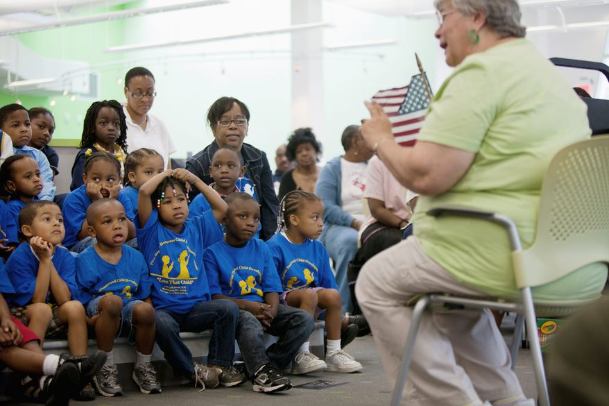 A librarian at the Deanwood Neighborhood Library in D.C., talks June 16, 2011, to a group of kindergarten students from nearby Houston Elementary School about the Pledge of Allegiance. (Pratik Shah/The Washington Times)