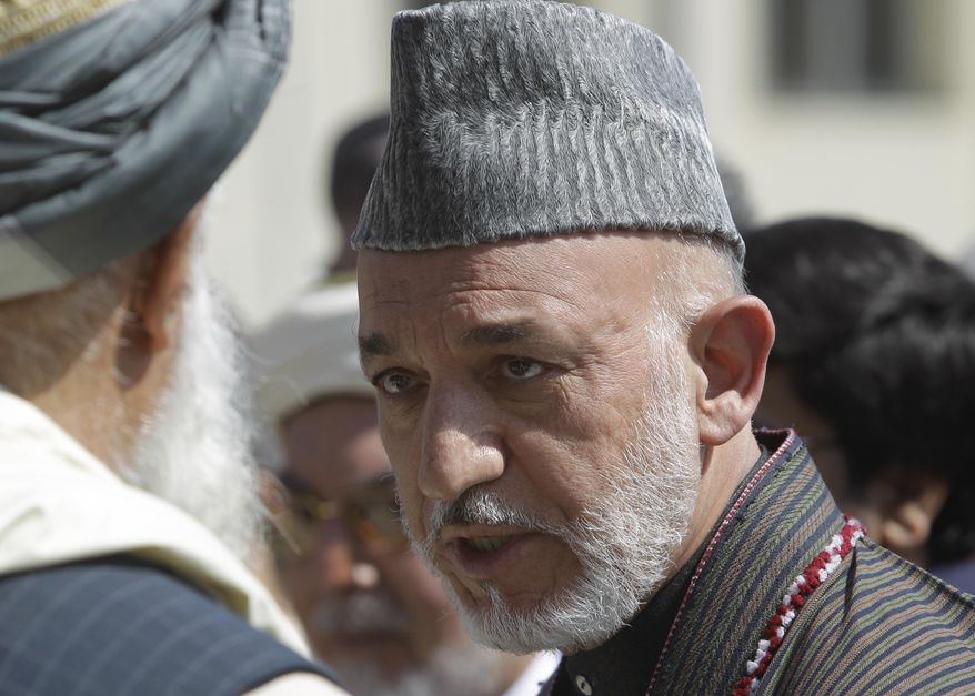 ** FILE ** Afghan President Hamid Karzai talks to one of elders during the funeral ceremony of former president Burhanuddin Rabbani at the presidential palace in Kabul, Afghanistan, Friday Sept. 23, 2011. (AP Photo/Kamran Jebreili)