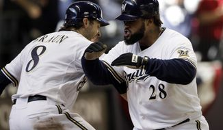 Milwaukee Brewers' Prince Fielder (28) celebrates with Ryan Braun (8) after Fielder hit a two-run home run during the seventh inning of Game 1 of baseball's National League division series against the Arizona Diamondbacks Saturday, Oct. 1, 2011, in Milwaukee. (AP Photo/David J. Phillip)
