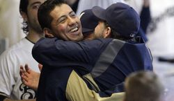 Milwaukee Brewers starting pitcher Yovani Gallardo, left, is congratulated in the dugout by pitching coach Rick Kranitz and Shaun Marcum, right, after throwing in the eighth inning of Game 1 of baseball's National League division series against the Arizona Diamondbacks Saturday, Oct. 1, 2011, in Milwaukee. (AP Photo/David J. Phillip)