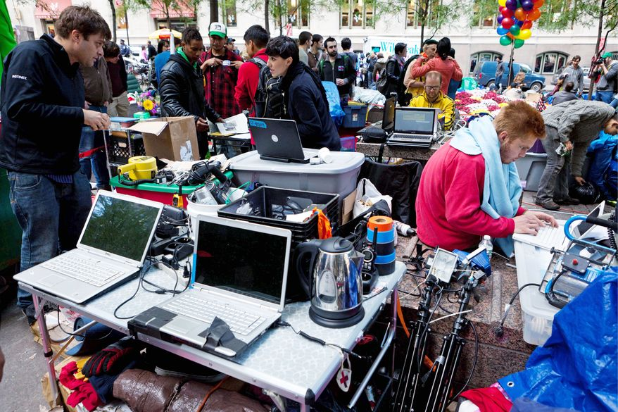 Demonstrators with Occupy Wall Street use the media area Sunday to coordinate news updates on laptop computers in the Manhattan financial district's Zuccotti Park. The protest has grown to include thousands of people in communities across the country. (Associated Press)