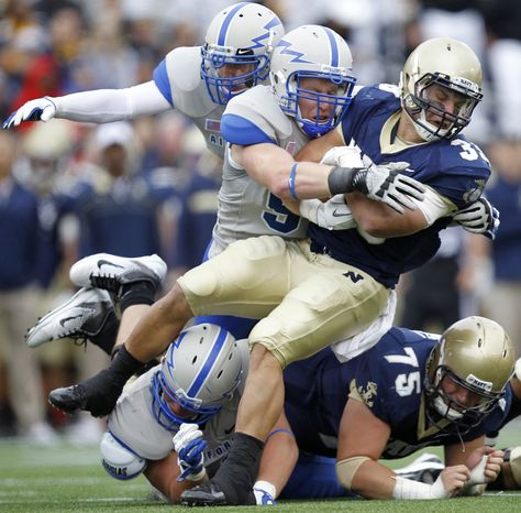 Navy fullback Alexander Teich, tight, is tackled by Air Force defensive lineman Harry Kehs during the second quarter of an NCAA college football game, Saturday, Oct. 1, 2011, in Annapolis, Md. Air Force won 35-34 in overtime.