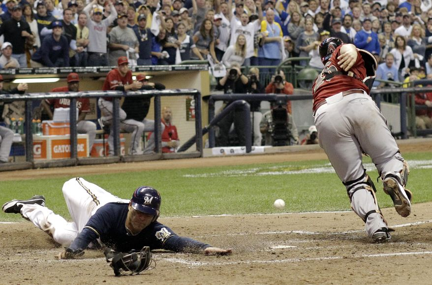 Arizona Diamondbacks catcher Miguel Montero can't catch the throw as Milwaukee Brewers' Jerry Hairston Jr. scores from third on a squeeze bunt by Jonathan Lucroy during the sixth inning of Game 2 of baseball's National League division series Sunday, Oct. 2, 2011, in Milwaukee. (AP Photo/David J. Phillip)