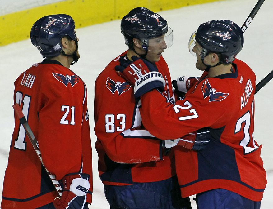 Washington Capitals' Jay Beagle (83) celebrates with teammates Karl Alzner (27) and Brooks Laich (21) after scoring a goal on an empty net during the third period of an NHL preseason hockey game against Chicago Blackhawks, Sunday, Oct. 2, 2011, in Washington. The Capitals won 4-1. (AP Photo/Luis M. Alvarez)