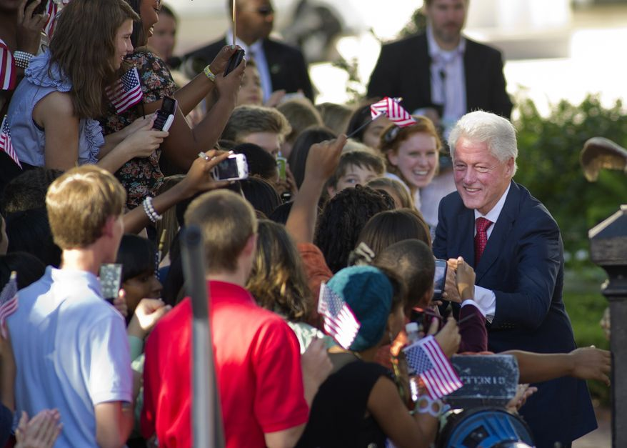 Former President Bill Clinton is greeted by well-wishers as he arrives at a celebration of the 20th anniversary of his announcement that he would run for President of the United States, Saturday, Oct. 1, 2011, in Little Rock, Ark. Bill Clinton is using the 20th anniversary of the launch of his presidential bid to offer a vigorous defense of President Barack Obama against what he calls the same anti-government stance he faced during his campaign and presidency. (AP Photo/Brian Chilson)