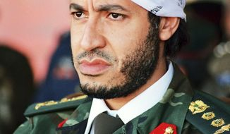** FILE ** In this undated photo made available Sunday, Sept. 25, 2011, al-Saadi Gadhafi, son of Libyan leader Moammar Gadhafi, watches a military exercise by the elite military unit commanded by his brother, Khamis, in Zlitan. (AP Photo/Abdel Magid al-Fergany, File)