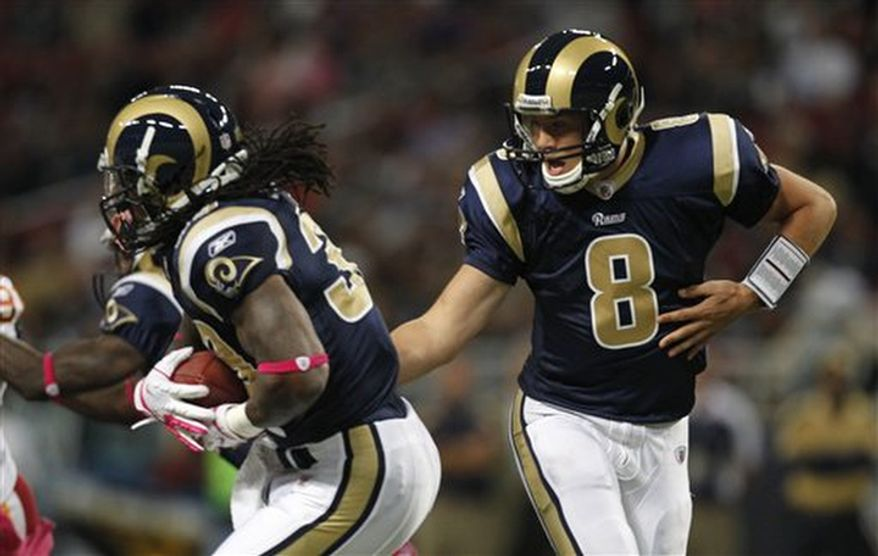 St. Louis Rams quarterback Sam Bradford, right, hands off to running back Steven Jackson during the first quarter of the NFL football game against the Washington Redskins Sunday, Oct. 2, 2011, in St. Louis. (AP Photo/Jeff Roberson)