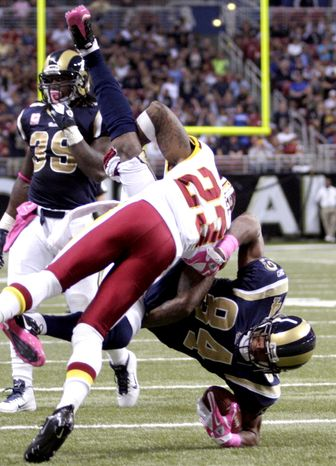 St. Louis Rams wide receiver Danario Alexander (84) is driven into the ground by Washington Redskins cornerback DeAngelo Hall (23) after catching a pass during the fourth quarter Sunday, Oct. 2, 2011, in St. Louis. Hall was flagged for an unnecessary roughness penalty and the Redskins went on to win 17-10. (AP Photo/Tom Gannam)