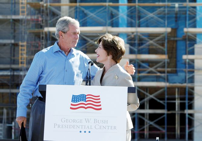 "** FILE ** Former first lady Laura Bush introduces her husband, former President George W. Bush, at the ""topping out"" ceremony of his library on the campus of Southern Methodist University in Dallas. (Associated Press)"