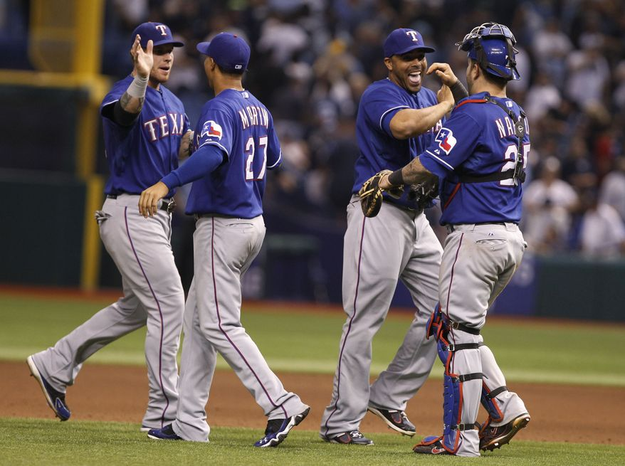Texas Rangers catcher Mike Napoli, right, congratulates Nelson Cruz, as Leonys Martin (27) congratulates Josh Hamilton,left, at the end of Game 3 of baseball's American League division series against the Tampa Bay Rays, Monday Oct. 2011 in St. Petersburg, Fla. The Rangers won 4-3 to lead the series 2-1. (AP Photo/Lynne Sladky)