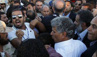 **FILE** In this photo from Sept. 10, 2011, Libya security argue during the arrival of Libyan Transitional National Council chairman Mustafa Abdel Jalil (center) at Metiga airport in Tripoli, Libya. (Associated Press)