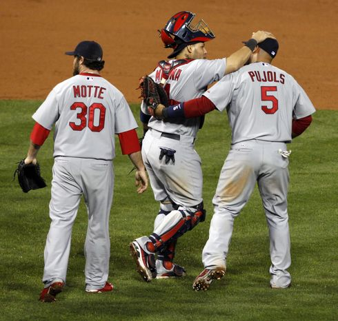 St. Louis Cardinals relief pitcher Jason Motte (30), Yadier Molina (4), and Albert Pujols (5) react after baseball's Game 2 of the National League division series with the Philadelphia Phillies Monday, Oct. 3, 2011 in Philadelphia. The Cardinals won 5-4. (AP Photo/Mel Evans)