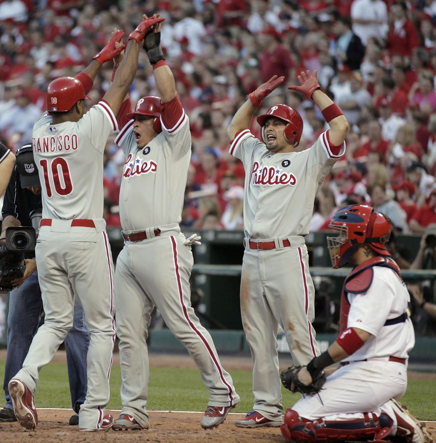 Philadelphia Phillies' Ben Francisco (10) celebrates with Shane Victorino, right, and Carlos Ruiz, center, after hitting a three-run home run with during the seventh inning of Game 3 of baseball's National League division series against the St. Louis Cardinals on Tuesday, Oct. 4, 2011, in St. Louis. (AP Photo/Charlie Riedel)