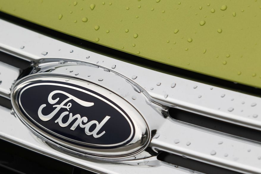** FILE ** This Aug. 31, 2011, photo, shows raindrops on the grill of a Lime Squeeze Metallic 2012 Ford Fiesta SE at the Maroone Ford of Miami dealership. (AP Photo/Wilfredo Lee)
