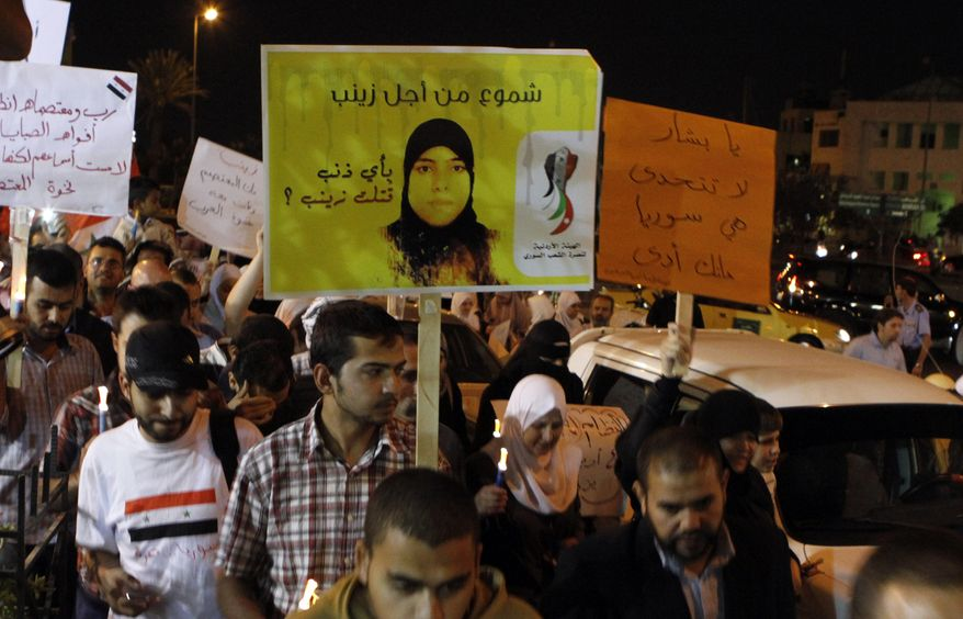 Syrians and Jordanians carry candles and posters depicting 18-year-old Zainab al-Hosni, believed to be the first woman to die in Syrian custody since the uprising began in mid-March, during a candlelight vigil in front the Syrian embassy in Amman, Jordan, on Oct. 3, 2011. (Associated Press)