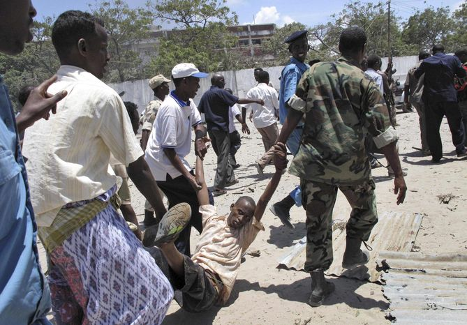 Somalis carry a wounded man at the scene of an explosion in Mogadishu, Somalia, Tuesday, Oct. 4, 2011. A rescue official says at least 55 people were killed after a car laden with explosives blew up in front of the Ministry of Education in the Somali capital of Mogadishu. (AP Photo/Mohamed Sheikh Nor)