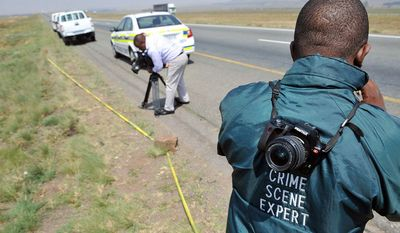 The crime scene on an isolated stretch of highway where Mark Andrews was found fatally shot is cordoned off Sept. 28 by police near Johannesburg. Andrews, a business partner of a strip-joint owner killed in May 2010, was slain execution-style. (Associated Press)