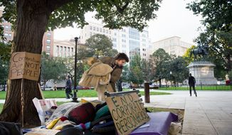 "Eric Sponaugle of Olney packs up his blanket Wednesday morning after sleeping near McPherson Square as part of the ""Occupy D.C."" protest. The protesters' complaints - corporate greed, corruption and social injustice - are vaguely defined, but they attract a wide swath of disaffected supporters. (Andrew Harnik/The Washington Times)"