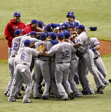 Members of the Texas Rangers celebrate their 4-3 win over the Tampa Bay Rays in Game 4 of the ALDS, Tuesday Oct. 4, 2011, in St. Petersburg, Fla. The victory gave the Rangers a 3-1 series win. (AP Photo/Mike Carlson)