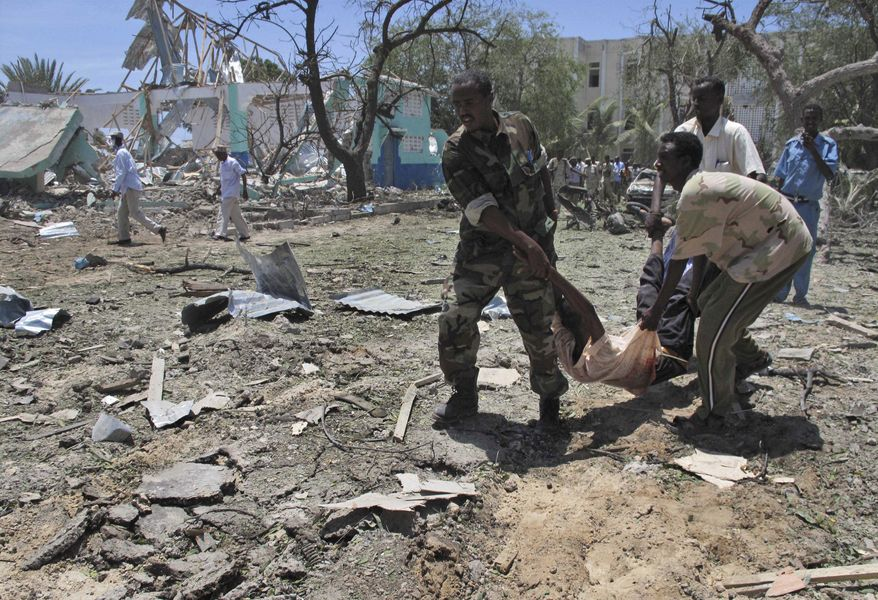 Somalis carry a wounded man at the scene of an explosion in Mogadishu, Somalia, on Tuesday, Oct. 4, 2011.  The al-Qaeda-linked militant group al-Shabab immediately claimed responsibility for the attack after more than a month of relative calm in the Somali capital. (AP Photo/Mohamed Sheikh Nor)