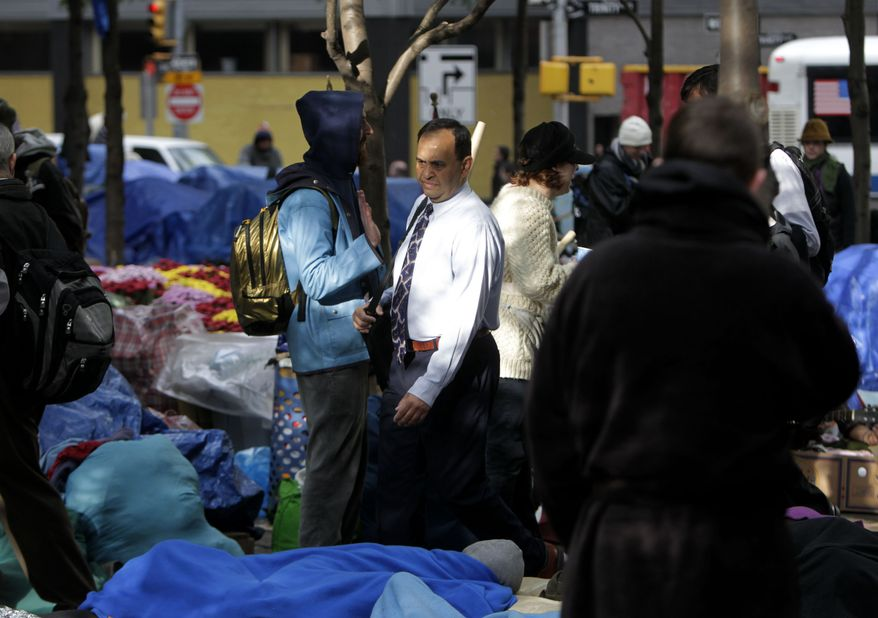 A commuter (center) walks through Zuccotti Park in New York's Financial District, where Occupy Wall Street protesters are encamped, on Tuesday, Oct. 4, 2011. (AP Photo/Seth Wenig)