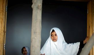 A girl peeks out of a window of her school in Kandahar, Afghanistan. The Taliban denied schooling to girls, so progress has been made, but the school director says his life is constantly in danger.