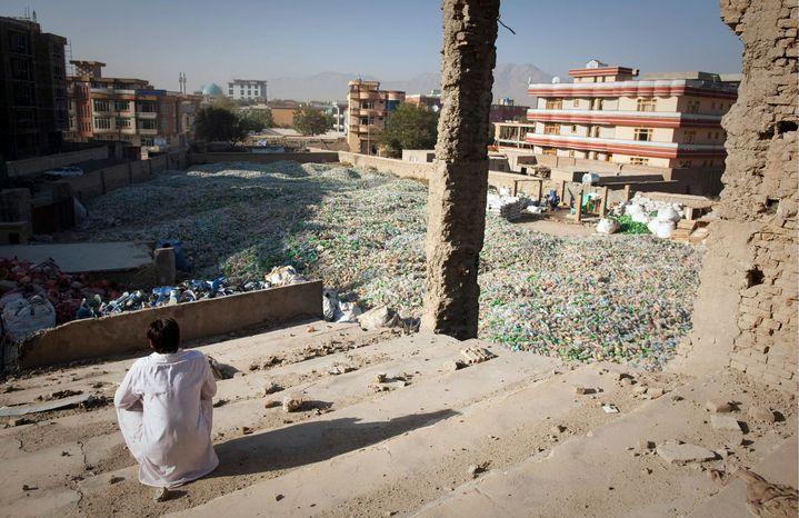 ASSOCIATED PRESS PHOTOGRAPHS Bilal Khan, 19, looks out at the center of Kabul from the Taliban-razed cinema his family, including nine sisters, has made their home. Six months of interviews show life is grim for the average Afghan.