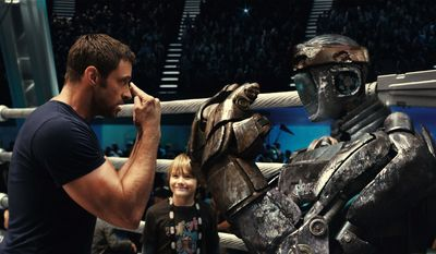 """Hugh Jackman as Charlie Kenton (left) gives fight instructions to one of his robot boxers as Dakota Goyo, who plays his son Max, looks on in a scene from from """"Real Steel."""" (Disney/Dreamworks II photograph via Associated Press)"""