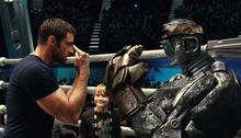 "Hugh Jackman as Charlie Kenton (left) gives fight instructions to one of his robot boxers as Dakota Goyo, who plays his son Max, looks on in a scene from from ""Real Steel."" (Disney/Dreamworks II photograph via Associated Press)"