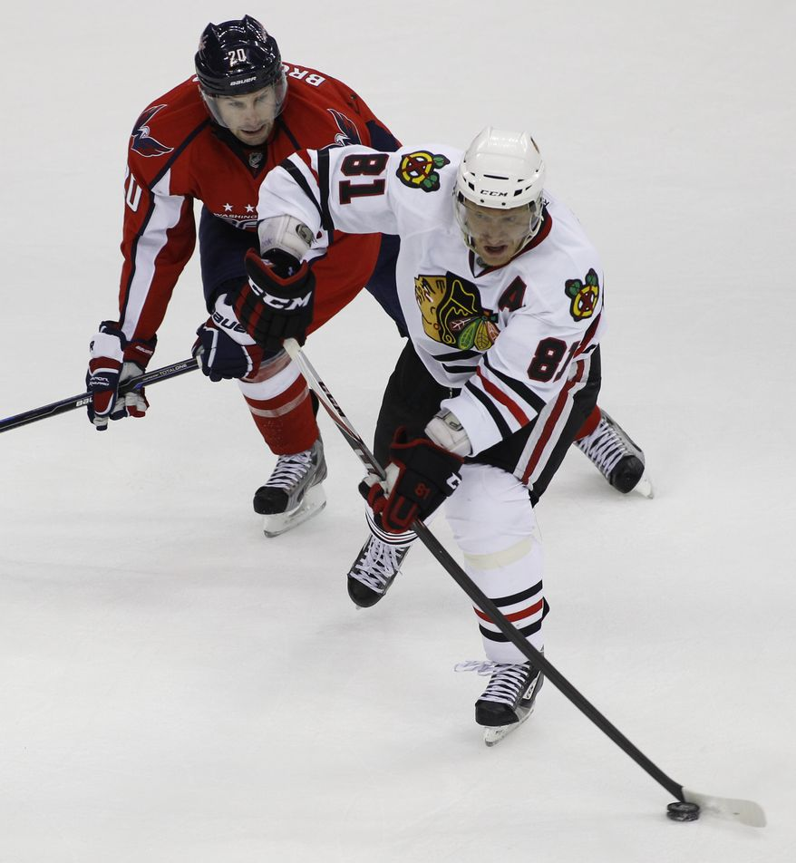 Chicago Blackhawks' Marian Hossa (81), of Slovakia, moves the puck as Washington Capitals' Troy Brouwer defends during the second period of an NHL preseason hockey game, Sunday, Oct. 2, 2011, in Washington. (AP Photo/Luis M. Alvarez)