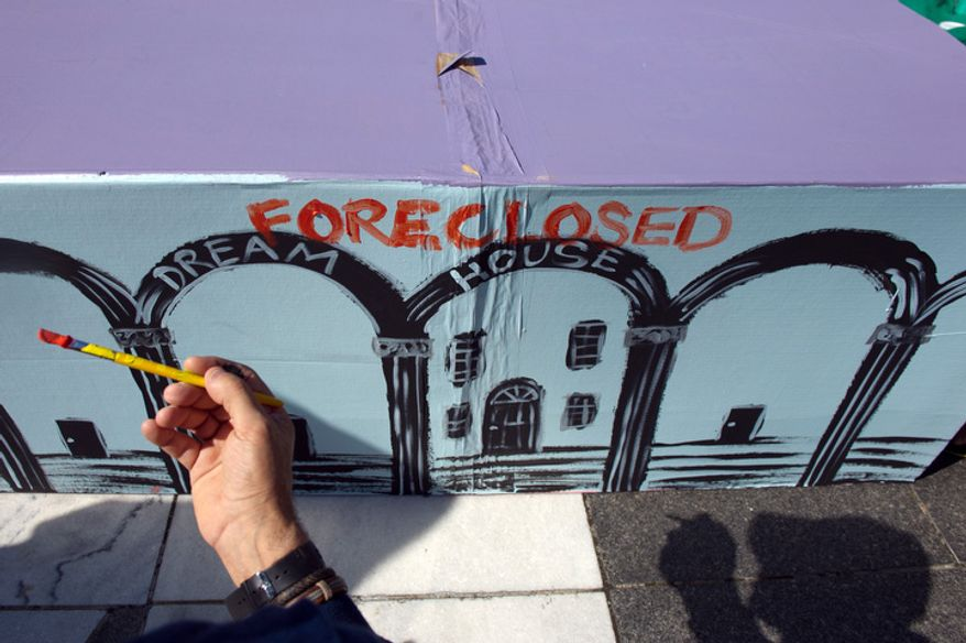 "Protester Andy Shallal of Washington paints ""Foreclosed"" on a cardboard house as hundreds of protesters gather at Freedom Plaza before marching to the White House in Washington on Thursday, Oct. 6, 2011. (Andrew Harnik/The Washington Times)"