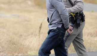 California Highway Patrol Officer Duane Nokes takes David Joseph Pedersen into custody following a traffic stop on Marysville Road and Gettys Court in Yuba City on Wednesday, Oct. 5, 2011. Pedersen and his girlfriend Holly Ann Grigsby are wanted for a murder in Washington state and the disappearance of a teenager in Oregon. (AP Photo/Appeal Democrat, David Bitton)