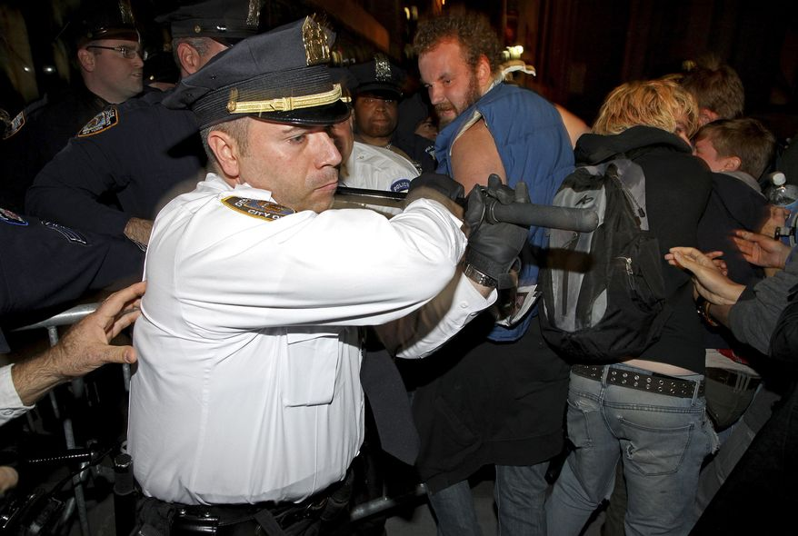 A New York City police lieutenant swings his baton as he and other police try to stop protesters who breached a barricade to enter Wall Street after an Occupy Wall Street march Wednesday, Oct. 5, 2011, in New York. (AP Photo/Craig Ruttle)
