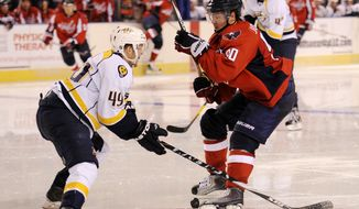 Washington Capitals' Marcus Johansson, of Sweden, (90) battles for the puck Nashville Predators' Ryan Ellis (49) during the second period of an NHL preseason hockey game, Tuesday, Sept. 20, 2011, in Baltimore. (AP Photo/Nick Wass)