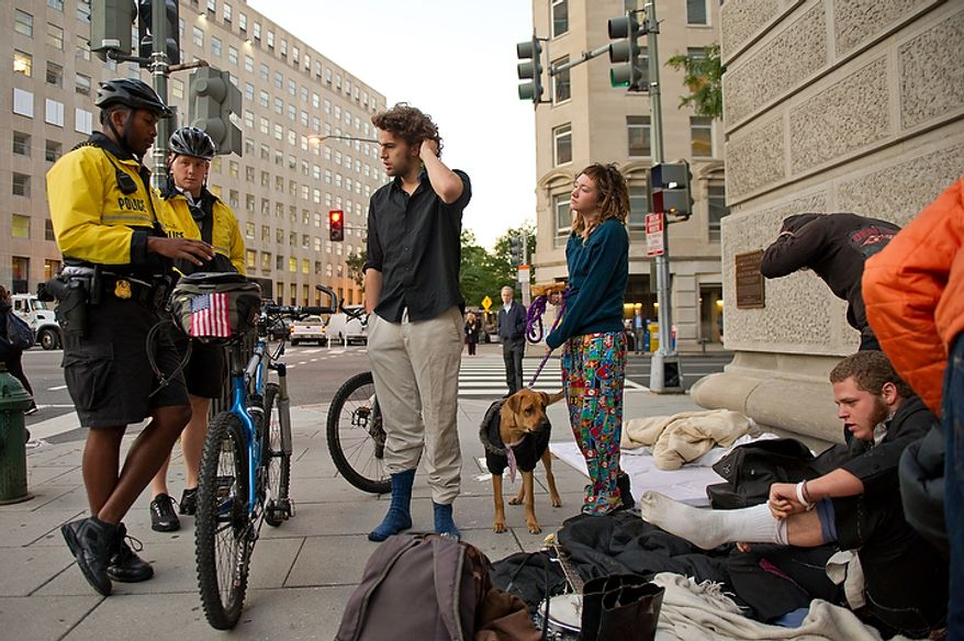 Protesters Eric Sponaugle, center, Colleen Clementine, second from right, and Banjo Youngblood, right, are woken and asked to move by police officers after spending the night near Mcpherson Square before  joining hundreds of protesters upset about a variety of issues from the ongoing wars in Afghanistan and Iraq to corporate greed and jobs gather at Freedom Plaza before marching to the White House, Chamber of Commerce and along K Street in NW Washington, DC, October 6,  2011. (Andrew Harnik / The Washington Times)